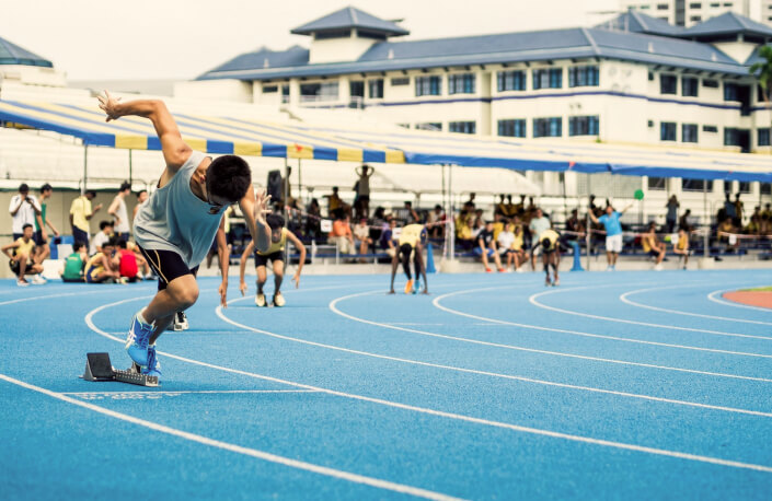 Athlete at starting block on a running track